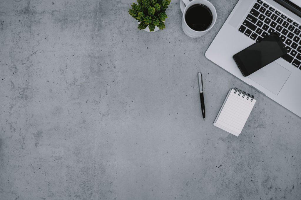 Ordenador portátil, bloc de notas y teléfono móvil en la mesa de trabajo