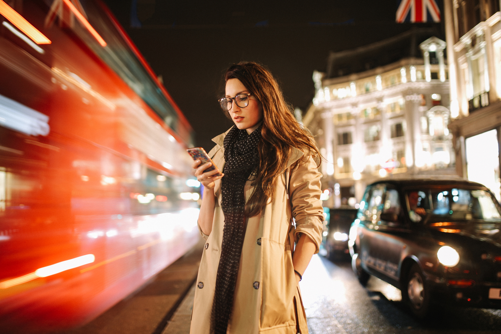 Portrait of a young woman on the busy streets of London downtown in the evening, texting for a cab