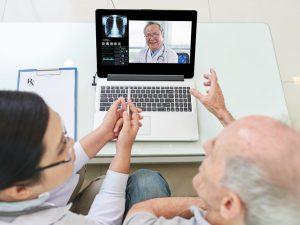 Hombre mayor y su médico con videoconferencia con trabajador médico experimentado